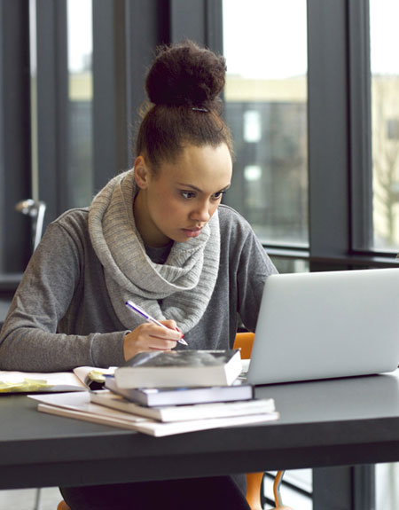 African American young woman working in a library with a laptop computer