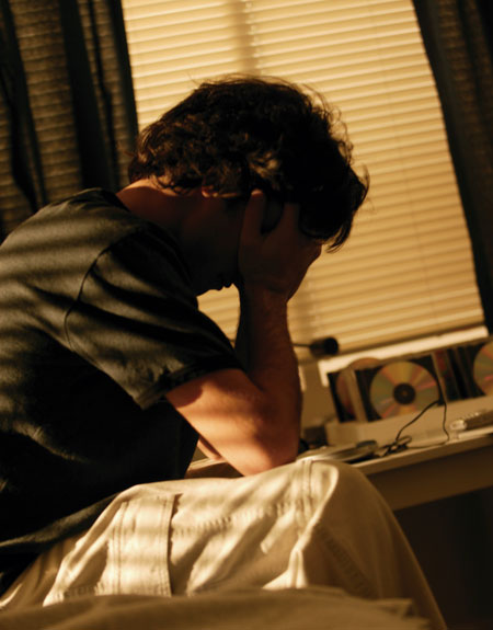 image of teen in his bedroom worried with his head in his hands