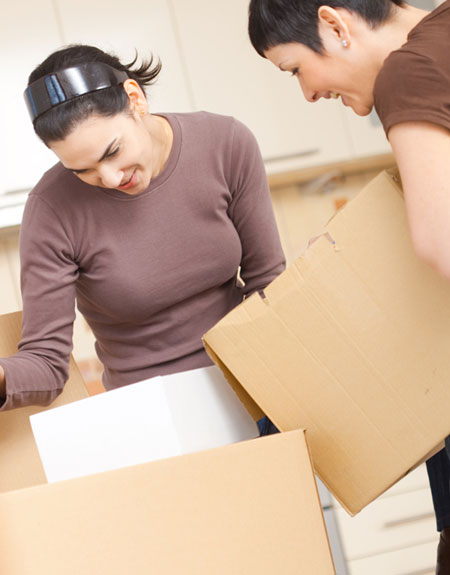 two young woman unpacking boxes in an apartment