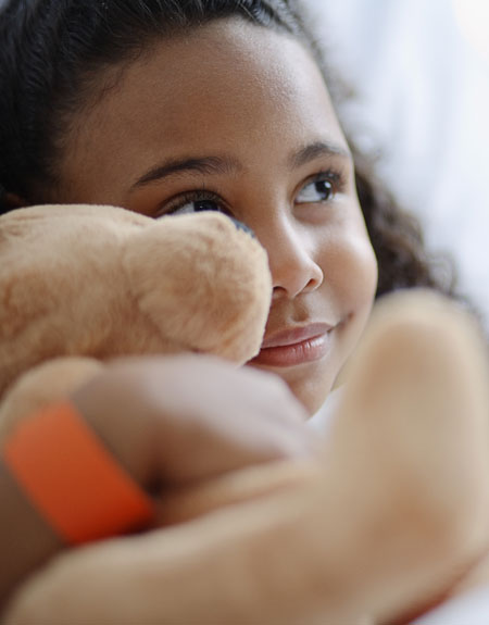 7 year old Latina girl hugging a teddy bear