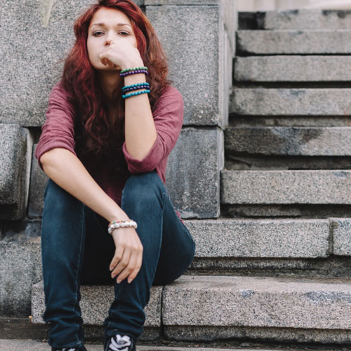 young girl depressed sitting on concrete stairs outside