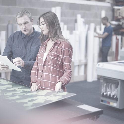 teen being taught work skills in printing shop